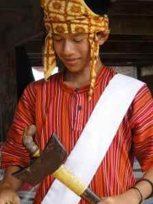 Adolescent boy holding ceremonial axe. Tana Toraja, Sulawesi, Indonesia.