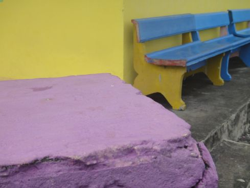 Pink oven against yellow wall with bright blue bench: house detail, Pulau Ternate, Moluku, Indonesia.