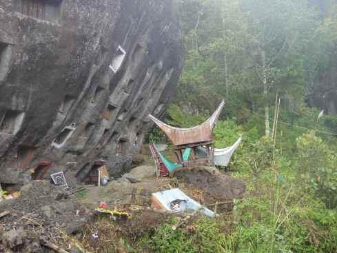 Broken graves in the shape of tongkonan houses below cave grave outcrop. Lokomata, Tana Toraja, Sulawesi, Indonesia.