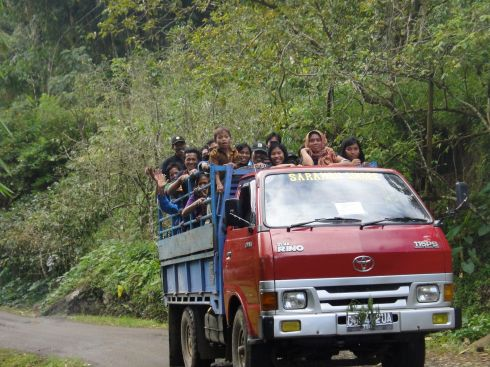 Torajans waving from cattle truck en route to funeral. Tana Toraja, Sulawesi, Indonesia.