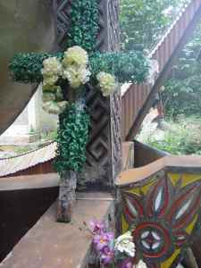 Crucifix rests against gigantic traditional grave: Tana Toraja, Sulawesi, Indonesia.