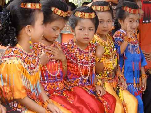 Five little girls in make up, headdresses, silk frocks and bead adornments wait to receive guests at their grandfather's funeral: Tana Toraja, Sulawesi, Indonesia.