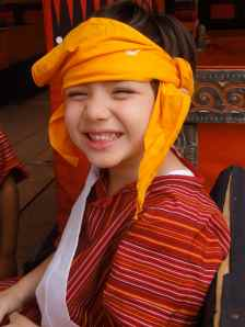 Little boy in gold turban, striped funeral outfit and white sash grins for the camera. Torajan funeral, Tana Toraja, Sulawesi, Indonesia.