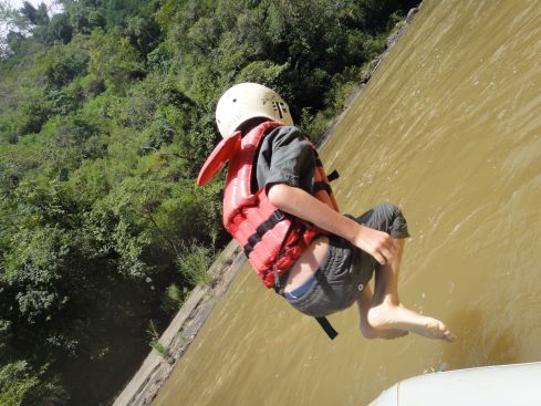 Z leaping from the edge of raft into Maiting River, wearing helmet and lifejacket. Tana Toraja, Sulawesi, Indonesia.