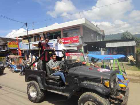 Local politician in Nehru jacket delivers royal wave, standing in 4WD. Rantepao, Sulawesi, Indonesia.