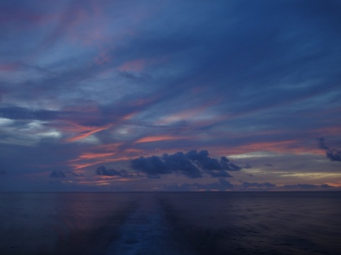 dazzling sunset over the Maluku Sea: blues, pinks, and the wake of a ferry.