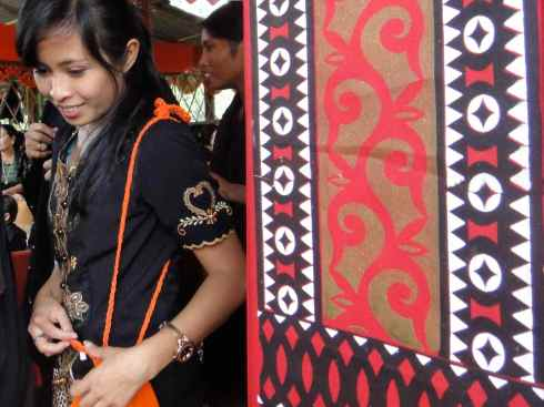 Beautiful young woman in black, with orange handbag besides fabric patterned wall, smiles at children. Torajan funeral, Tana Toraja, Sulawesi, Indonesia.