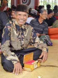 Mourner opens box full of kretek cigarettes in family area at Torajan funeral: Tana Toraja, Sulawesi, Indonesia.