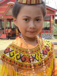 Torajan girl at funeral in yellow silk and beaded head dress: Tana Toraja, Sulawesi, Indonesia.