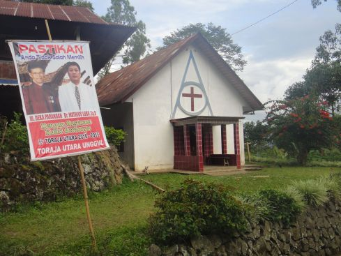 Political poster stands on easel by church in Tana Toraja, Sulawesi, Indonesia.