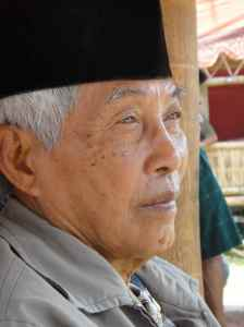 Elderly dignitary in Islamic prayer hat at Torajan funeral, Tana Toraja, Sulawesi, Indonesia.