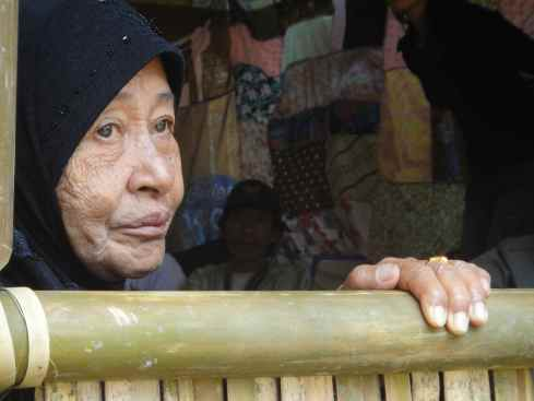 Elderly woman in dark headscarf framed by bamboo structure at Torajan Funeral, Tana Toraja, Sulawesi, Indonesia.