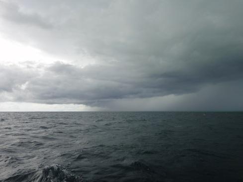 Storm clouds gather over a flat dark sea. Off Pulau Derawan, Indonesia.