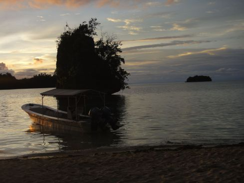 Sunset over Pulau Kadidiri Indonesia, illuminating the tiny islet near the shore.