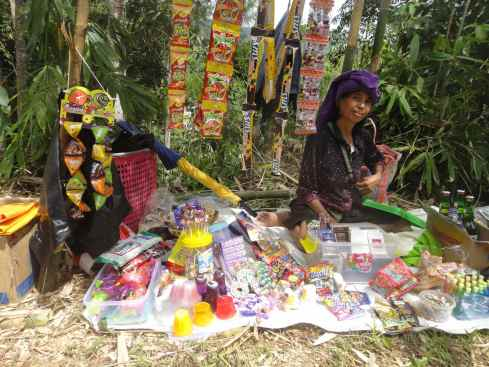 Woman selling sweets and candies outside funeral. Tana Toraja, Sulawesi, Indonesia.