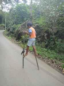 Torajan boy racing along the street on bamboo stilts. Tana Toraja, Sulawesi, Indonesia.