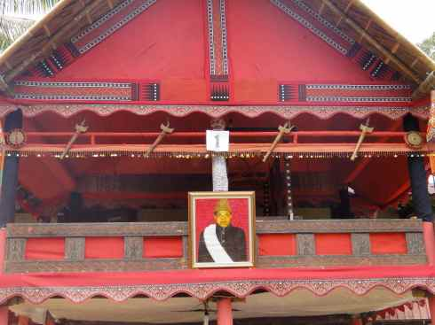 Scarlet balcony decorated with axes and portrait of the deceased. Tana Toraja funeral. Sulawesi, Indonesia.