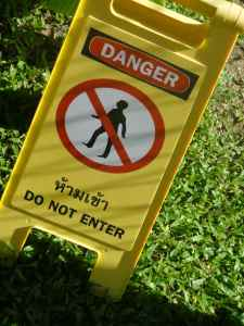 """Sign reading """"danger do not enter"""" with a picture of a person struck through."""