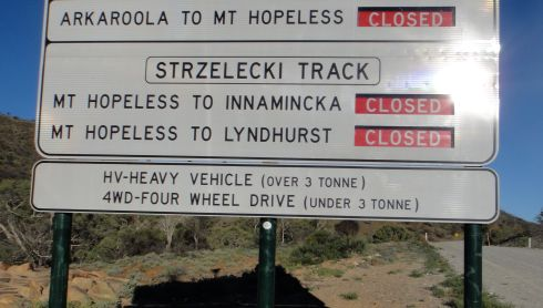 Sign in the Australian outback, indicating that roads to and from Mount Hopeless are closed.